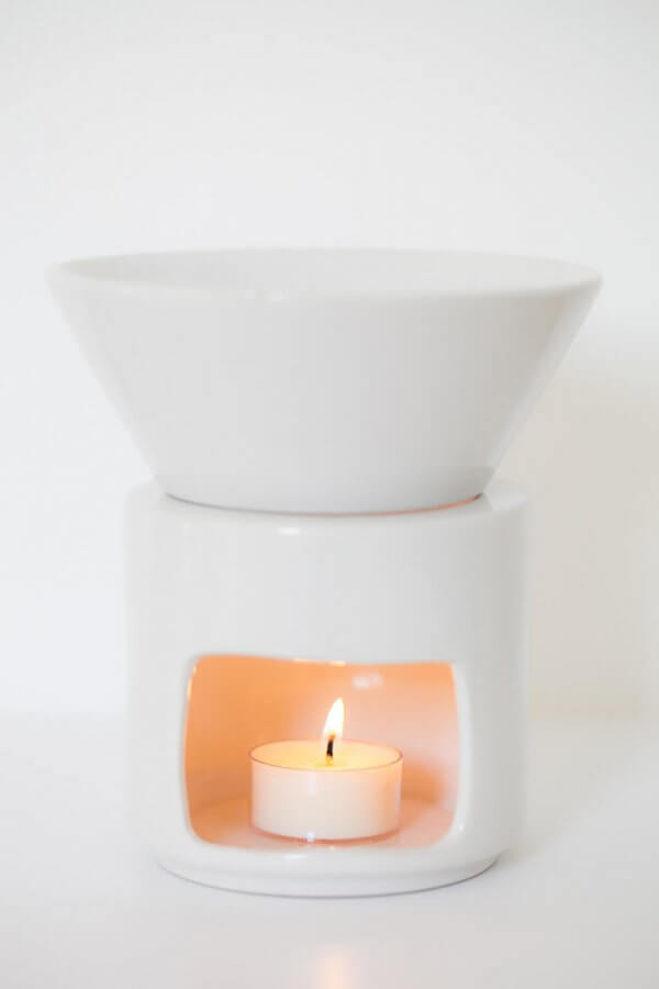 Large white ceramic oil burner with lit tealight candle inside