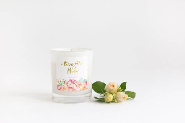 I Love You Mum Soy Candle In White Glass With Peony And Marshmallow Scent By Lemon Canary. Beside a small bunch of light coloured roses.